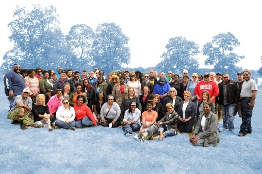 LMHA Staff group photo taken outside some sitting on ground, some standing about 60 people